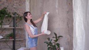 Hushållsarbete nätt brunettägare som hemma rullar ut den nya tapeten på väggen under reparationer