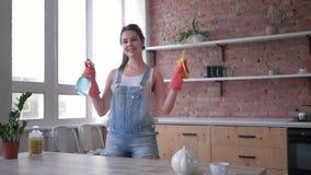 Hushållsarbete och hushållning, den härliga kvinnan i handskar med rengöringsmedelsprej och dammtrasafrikänder bordlägger s