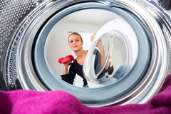 Hushållsarbete: ung kvinna som gör tvätterit royaltyfri bild