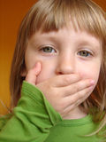 Hush. Cute blond girl with her hand over her mouth Stock Photo