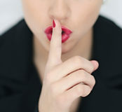 Hush. Isolated woman's hand and lips hushing or quieting her audience stock photo
