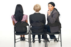 Hush!Be quiet!. Three business women sitting on chairs viewing a presentation and one of them return her head to  tell you to be quiet Stock Photo