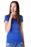 Hush be quiet. Hush be quiet woman isolated. Teen girl with finger on her lips looking on side and smiling Stock Image