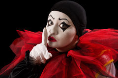 Hush be quiet. Funny Pierrot with her finger against her mouth Stock Photos