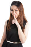 Hush be quiet woman isolated. Beautiful mixed race caucasian / chinese young woman isolated in full length on white background Stock Image