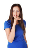 Teen girl with finger on her lips. Royalty Free Stock Photo