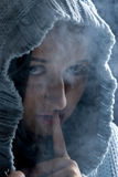 Hush!Hidden woman in smoke. Head of young woman with hood wool in night with many smoke around her standing with finger at mouth like she say: sssst ,be quiet! Royalty Free Stock Images