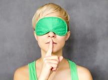 Hush hush. Portrait of young beautiful woman in sleep mask making hush sign Royalty Free Stock Photography