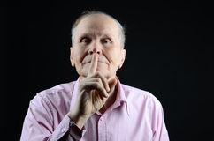 Hush!. Senior showing the sign not to speak Royalty Free Stock Image