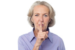 Hush...Silence please!. Senior woman gesturing silence over white Royalty Free Stock Photography