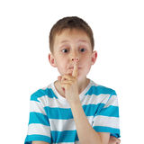 Hush! - Tense boy with big eyes, finger by lips. Portrait of a kid, white boy with big eyes and tense face, touching lips by a finger - QUIET gesture: hush! sh! Stock Photo