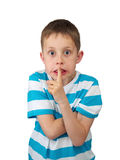 Hush! Tense boy with bulging eyes, finger by lips. Portrait of a kid, blond boy with big eyes and tense face, touching lips by a finger, isolated on white Royalty Free Stock Photography