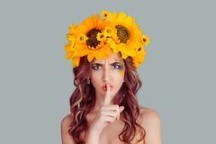 Woman with floral headband wide eyed asking for silence, secrecy stock photography