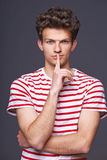Hush. Young serious sullen man with finger on lips Royalty Free Stock Photography