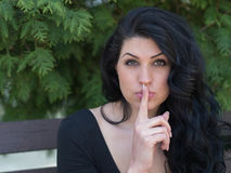 Hush. Young woman with finger on her lips Stock Photo