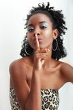 Hushing gesture. Beautiful African American woman with a large afro hairdo making a hushing gesture holding her finger to her lips as she requests silence Stock Photography