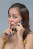 Hushing girl with cellphone Stock Image