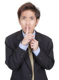 Hushing oriental businessman. Young Chinese businessman hushing with fingers on lips and a mesmerizing urging gaze insisting on discretion and secrecy. Isolated Royalty Free Stock Photos
