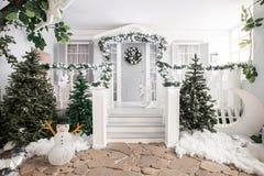 Husingång som dekoreras för ferier julen dekorerar nya home idéer för garnering till girland av granträdfilialer och ljus på räck royaltyfri fotografi