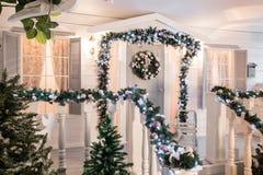 Husingång som dekoreras för ferier julen dekorerar nya home idéer för garnering till girland av granträdfilialer och ljus på räck arkivfoton