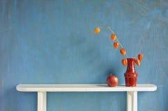 Husk tomato  plant flowers in vase on white wooden shelf Stock Photo