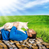 Husky dog puppy playing with happy man Royalty Free Stock Photos