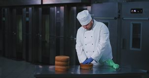 A husky good looking baker guy with proper chefs attire cuts the cake in half and checks for the consistency as there. Are ovens in the background. slow stock video footage