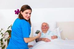 Häusliche Pflege - Blutdruckmessen Stockbilder
