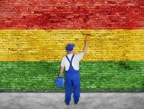 Husmålaren målar Reggaeflaggan på tegelstenväggen Royaltyfri Fotografi
