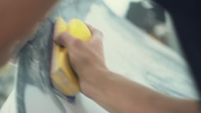 Husmålaren polerar manuellt yttersidan av bilen arkivfilmer