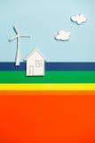 Husmodell och väderkvarn på färgrik bakgrund arkivfoto