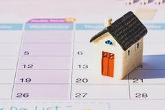 Husmodell på kalender planera besparingpengar av mynt f?r att k?pa ett hem- begrepp arkivfoton