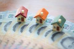 Husmodell på sedlar, sparande pengar för fastighetbegreppet, husmodell, för lönlån, begrepp av att köpa en försäljning, arrende, arkivbild