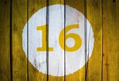 Husnummer eller kalenderdatum i den vita cirkeln på tonad guling Arkivfoton