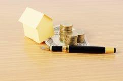 Huspapper med pengarmyntbunten och affärsreservoarpenna för Royaltyfri Fotografi