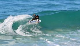 Huésped de la leche desnatada que monta una onda de la rotura de la orilla en la playa en Laguna Beach, California de Aliso Imágenes de archivo libres de regalías