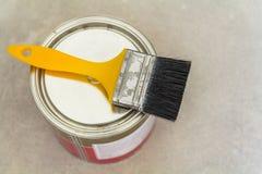 Husrenovering Kunna med målarfärg och ett borstehjälpmedel på konkreta lodisar royaltyfri fotografi