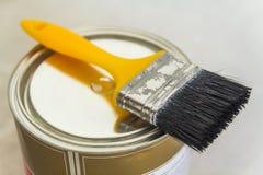 Husrenovering Kunna med målarfärg och ett borstehjälpmedel på konkreta lodisar royaltyfri bild