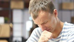 Husten des jungen kranken Mannes in den zufälligen Stoffen bei der Arbeit