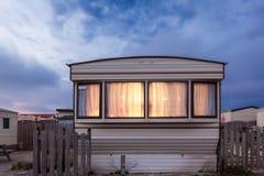 Husvagn som används som permanent hem på en släp parkerar på skymning arkivbild