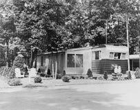 Husvagn som används som permanent hem i släp parkerar, 1956 (alla visade personer inte är längre uppehälle, och inget gods finns  Arkivfoto