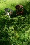 Hut auf geflochtenem Stuhl im Gras in der gescheckten Sonnenblende Lizenzfreies Stockfoto