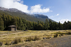 Hut below Mount Wellington, Tasmania. Low view of Mount Wellington in Hobart, Tasmania, with snow, small hut at the base of the mountain Royalty Free Stock Photography