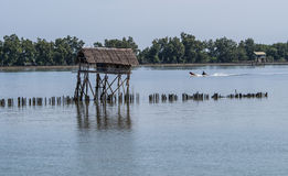 Hut and boat in the river. Near mangrove forest Stock Photos