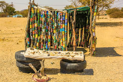 African hut. A hut in front of a stall with craft items for sale, located in a poor area near the Spitzkoppe Namibia. The Hunting lodge is made from cans of Royalty Free Stock Image