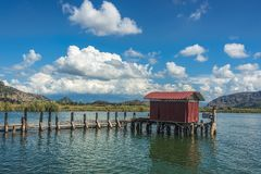 A hut on the end of a wooden pier on a lake with green reeds und. Er blue skies with fluffy white clouds Royalty Free Stock Photos