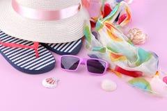 Hut, Flipflops und rosenrote Gläser mit Muscheln setzen Zubehör auf den Strand lizenzfreie stockfotografie