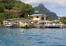 Hut at the foot of the mountain on the seashore and boat pier Royalty Free Stock Image