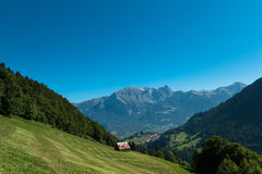 Hut in front of mountains. A little Swiss mountain hut is surrounded by massive mountains and forest Stock Image