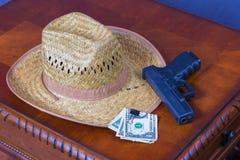 Hut, Geld und Pistole Stockfotos